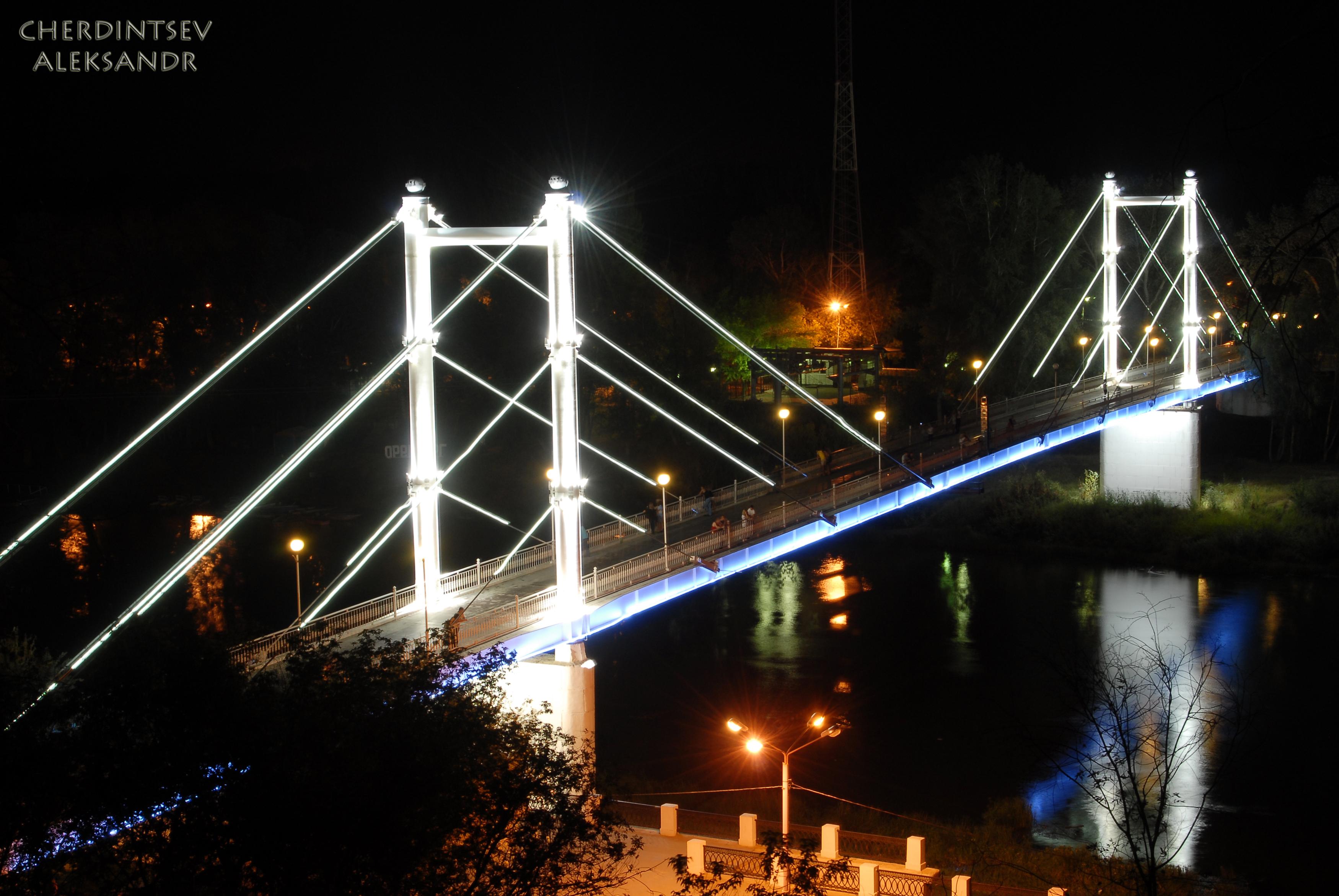 Фото и описание: пешеходный подвесной мост на набережной оренбурга. Одним из символов оренбурга является пешеходный мост через речку урал. Река урал символически делит город на европу и азию, о чем и свидетельствует стела на середине моста. Так что, проходя половину моста в европе,